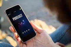 Frau, die im h?renden Podcast der Stra?e sitzt stockbilder