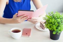 Frau, die im Hand-eReader Kindle Paperwhite hält Lizenzfreies Stockfoto