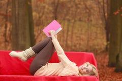 Frau, die im Herbstfallpark-Lesebuch sich entspannt Lizenzfreies Stockfoto