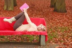 Frau, die im Herbstfallpark-Lesebuch sich entspannt Stockbild