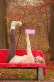 Frau, die im Herbstfallpark-Lesebuch sich entspannt Lizenzfreie Stockbilder
