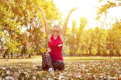 Frau, die im Herbstpark genießt stockbild