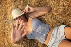 Frau, die im Heustapel sich entspannt Stockfotos