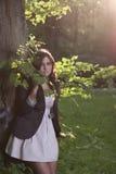 Frau, die im Holz am sonnigen Tag steht Stockfotografie