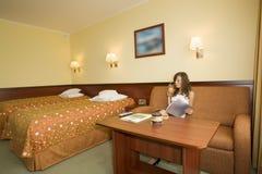 Frau, die im Hotelzimmer sitzt stockbilder