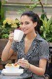 Frau, die im im Freienkaffee zu Mittag isst Stockfoto