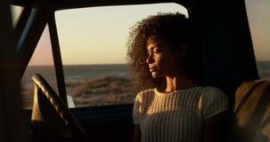 Frau, die im Kleintransporter am Strand 4k sitzt stock video