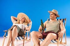 Frau, die im Klubsessel durch Mann mit Bier sitzt stockbild