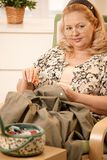 Frau, die im Lehnsessel näht Lizenzfreie Stockfotografie