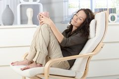 Frau, die im Lehnsessel sich entspannt Stockfotografie