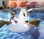 Frau, die im Luxusswimmingpoolurlaubshotel auf dem großen aufblasbaren Einhorn schwimmt Pegasus-Floss sich entspannt Stockbilder