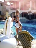 Frau, die im Luxusswimmingpoolurlaubshotel auf dem großen aufblasbaren Einhorn schwimmt Pegasus-Floss sich entspannt lizenzfreie stockfotos