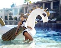 Frau, die im Luxusswimmingpoolurlaubshotel auf dem großen aufblasbaren Einhorn schwimmt Pegasus-Floss sich entspannt lizenzfreies stockfoto