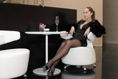 Frau, die im Luxuxinnenraum sitzt Stockbilder