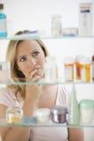 Frau, die im Medizin-Kabinett schaut Lizenzfreies Stockbild
