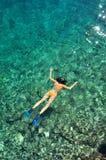 Frau, die im Meer im orange Bikini schnorchelt Lizenzfreie Stockbilder