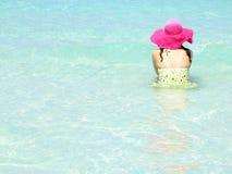 Frau, die im Meer sitzt Stockbild
