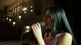 Frau, die im Mikrofon auf einem leeren Stadium singt stock video footage