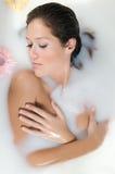 Frau, die im Milchbad mit Blumen sich entspannt Lizenzfreies Stockfoto