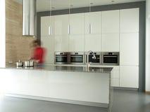 Frau, die im modernen Kücheinnenraum kocht Stockfoto