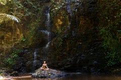 Frau, die im Naturwasserfall auf dem Felsen meditiert Lizenzfreie Stockbilder