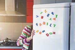 Frau, die im offenen Kühlschrank mit Familienbuchstaben schaut Stockbild