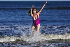 Frau, die im Ozean spielt und spritzt Lizenzfreies Stockfoto