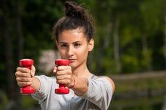 Frau, die im Park mit zwei roten Gewichten trainiert Lizenzfreies Stockfoto
