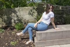 Frau, die im Park sitzt stockfoto