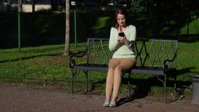 Frau, die im Park unter Verwendung des Smartphone sitzt stock footage
