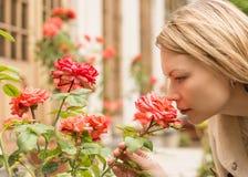 Frau, die im Park von Rosen steht Ein hübsches Mädchen, welches die blühenden Rosen riecht lizenzfreie stockfotos