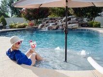 Frau, die im Pool mit Getränk sich entspannt lizenzfreie stockfotografie