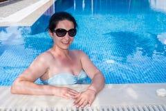 Frau, die im Pool sich entspannt Stockfoto