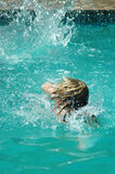 Frau, die im Pool spritzt Stockbild