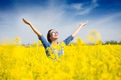Frau, die im Rapsfeld zujubelt Lizenzfreies Stockfoto