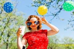 Frau, die im roten Kleid und in den gro?en lustigen Sonnenbrillen auf Gartenfest - Sommerpicknick aufwirft stockfoto