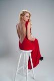 Frau, die im roten langen Kleid mit offenem Rücken auf Whit sitzt Lizenzfreie Stockfotografie