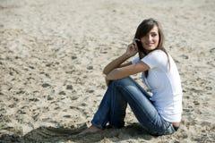 Frau, die im Sand mit einem Handy sitzt Stockfotos