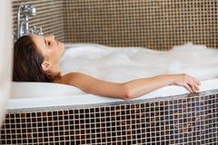 Frau, die im Schaumbad sich entspannt Frauenfuß im Wasser lizenzfreies stockbild