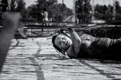 Frau, die im Schlammlauf und -Hindernislauf kämpft stockbild
