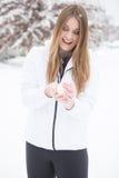 Frau, die im Schnee macht Schneebälle spielt Stockbild