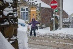 Frau, die im schneebedeckten Blizzard kämpft, um eine Straße zu kreuzen Stockbild