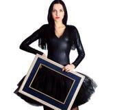 Frau, die im schwarzen Kleid hält Bilderrahmen trägt Lizenzfreies Stockfoto