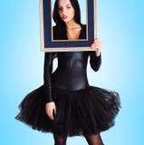 Frau, die im schwarzen Kleid hält Bilderrahmen trägt Stockfotografie