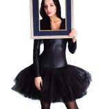 Frau, die im schwarzen Kleid hält Bilderrahmen trägt Lizenzfreies Stockbild