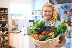 Frau, die im Shop mit Korb der Frischware arbeitet Lizenzfreies Stockbild