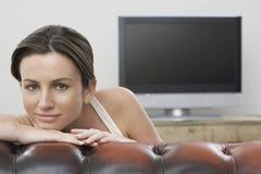 Frau, die im Sofa With Flat Screen Fernsehen im Hintergrund sich lehnt Lizenzfreie Stockfotografie