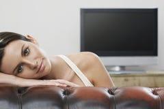 Frau, die im Sofa With Plasma Fernsehen im Hintergrund sich entspannt Lizenzfreies Stockfoto