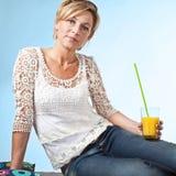 Frau, die im Sommer sitzt auf dem Boden mit einem Glas I sich entspannt Stockfotografie