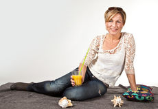 Frau, die im Sommer sitzt auf dem Boden mit einem Glas I sich entspannt Stockbild